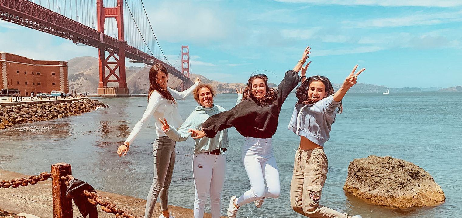 El grupo EMY del campamento de inmersión en San Francisco saludando con el Golden Gate de fondo