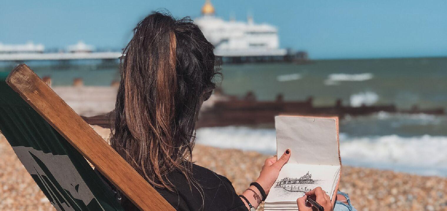 Alumnos del campamento de verano en Eastbourne posando en la playa con el Eastbourne Pier de fondo.