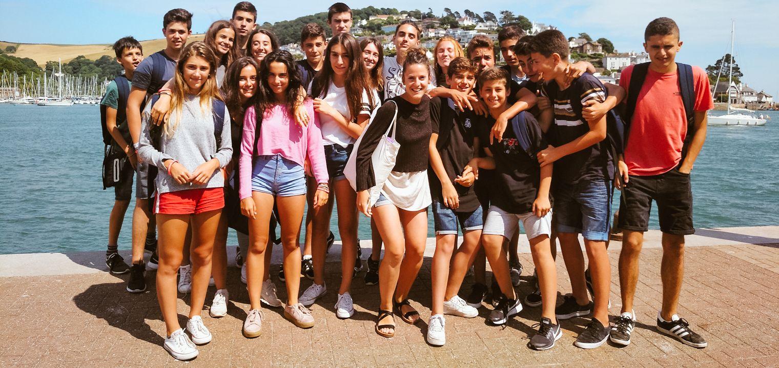 Grupo de estudiantes del campamento de inglés en Torquay posando alegres con la monitora